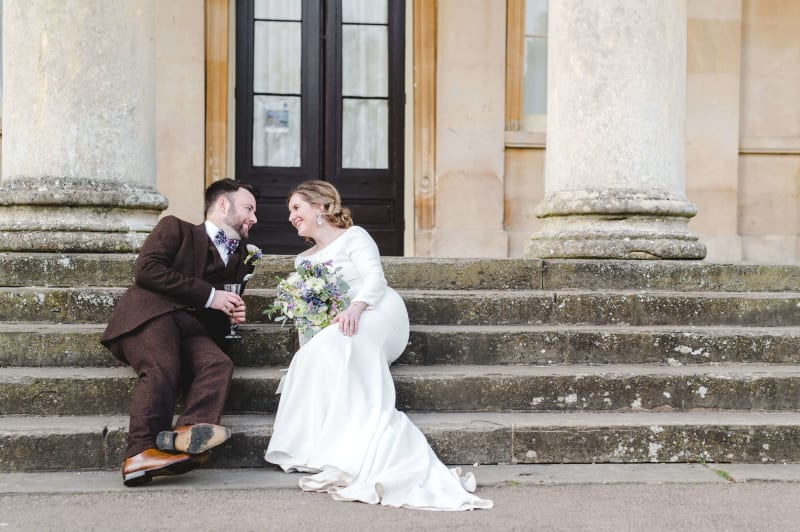 Adam and Faye Hughes sitting on steps in their wedding clothes