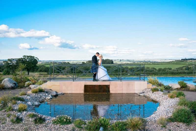 couple kisses on the bridge lake at radstone hotel