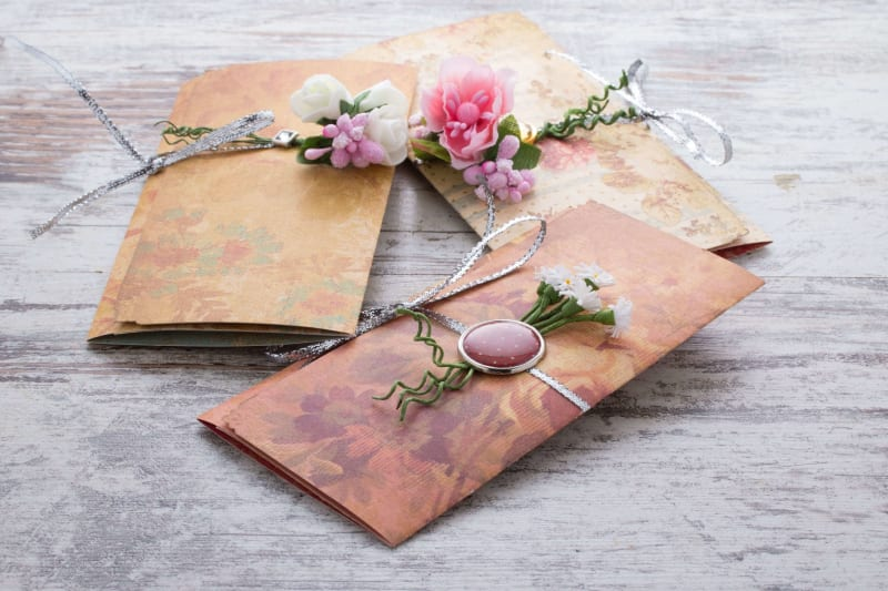 Wedding invitations with flowers presented on a wooden table