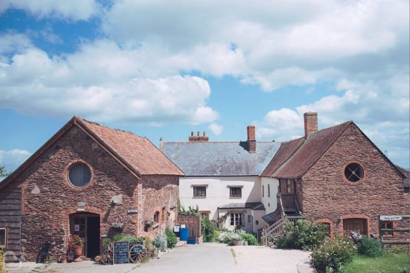 Huntstile Organic Farm with blue skies, a barn and farm wedding venue Somerset