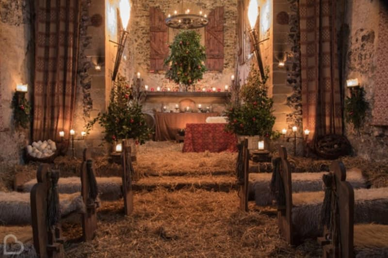 The Lost Village of Dode, an intimate wedding venue set up with hay and christmas trees for a wedding ceremony