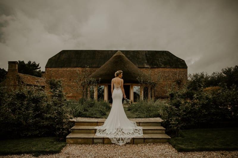 bride stands in front of brickhouse vineyard wedding venue