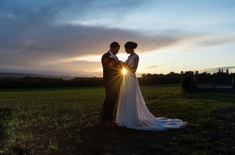 Married couple  standing in field at sunset