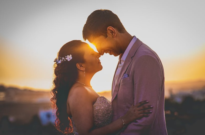 Married couple in love standing next to each other with sunset in background