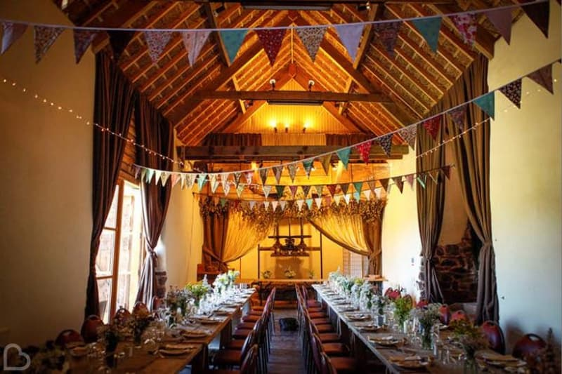 Duvale Priory, a wedding venue in Devon, decorated with flags and tables set for many wedding guests