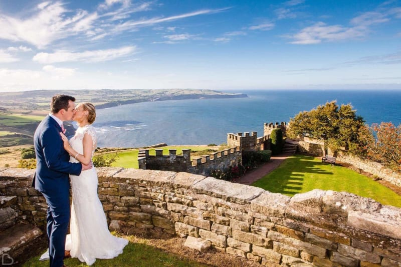newlyweds kiss with the sea behind them at raven hall