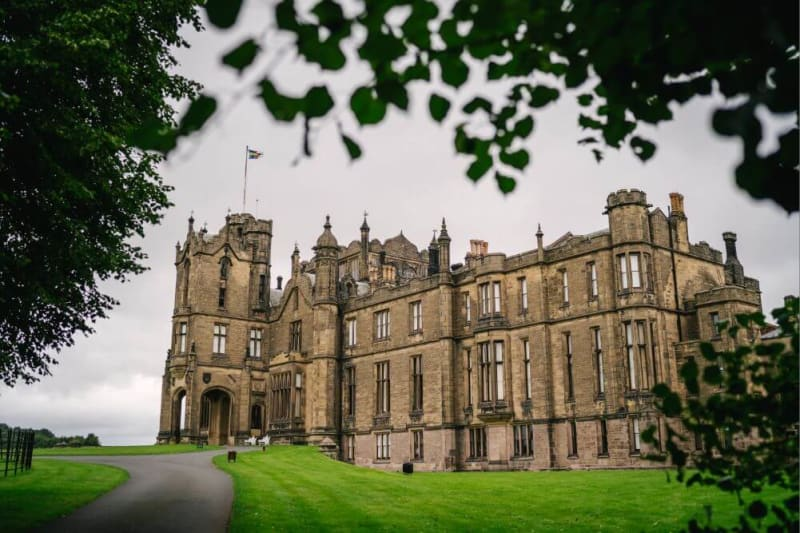 A big castle stands surrounded by well kept lawns.