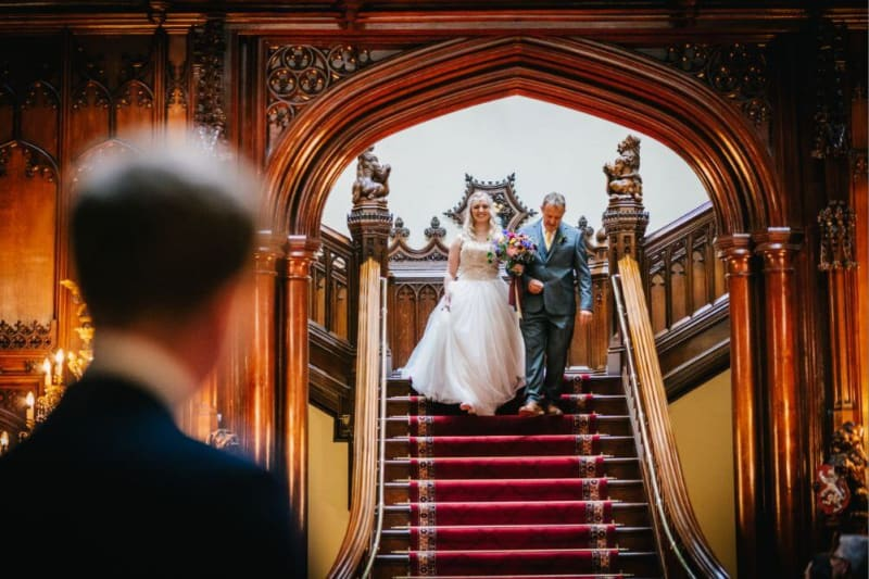 The bride and her father walk down a red staircase.