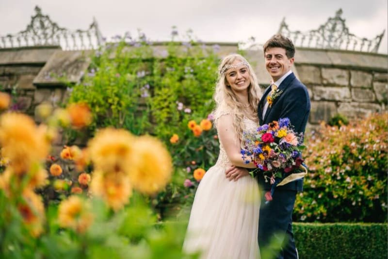 The bride and groom hold each other and smile outside surrounded by flowers.
