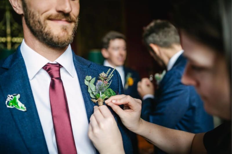 A lady fixes the flowers in one of the groomsmen jacket.