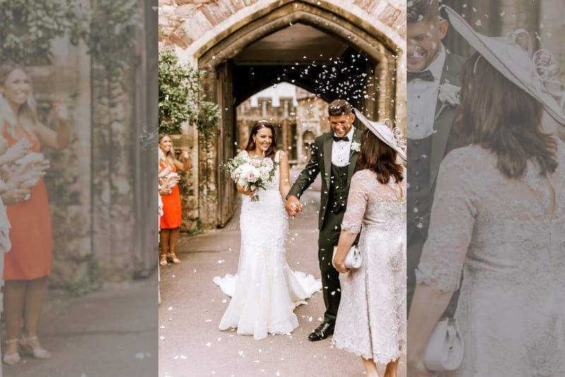 The bride and groom step outside smiling and holding hands as guests throw petals at them.