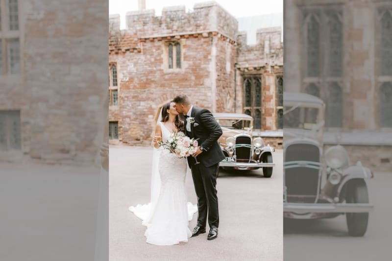The bride and groom kiss outside the castle.