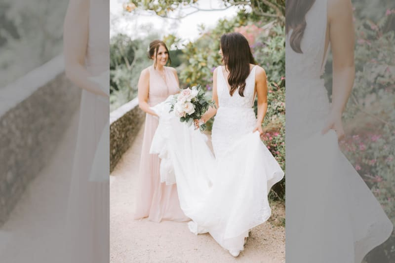The bridesmaid holds the bride's dress.