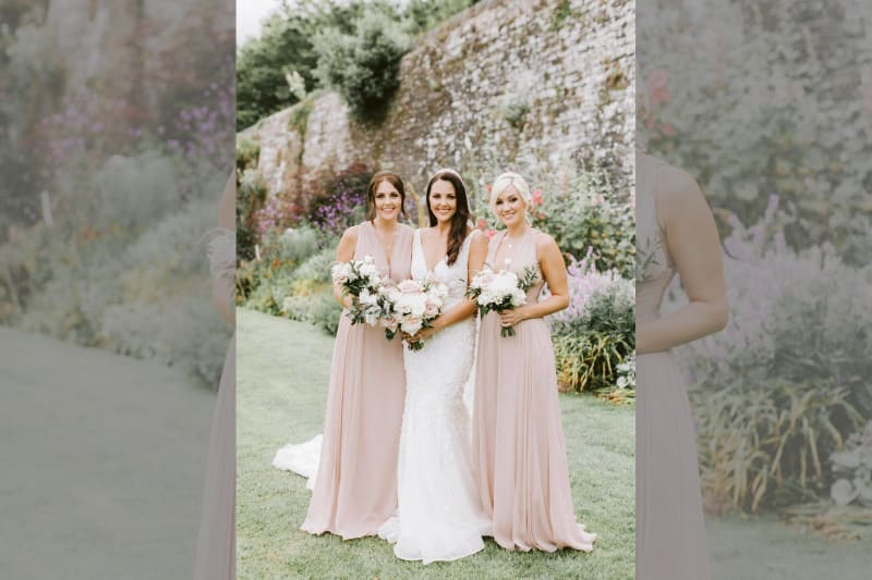 The bride posing with two bridesmaids.