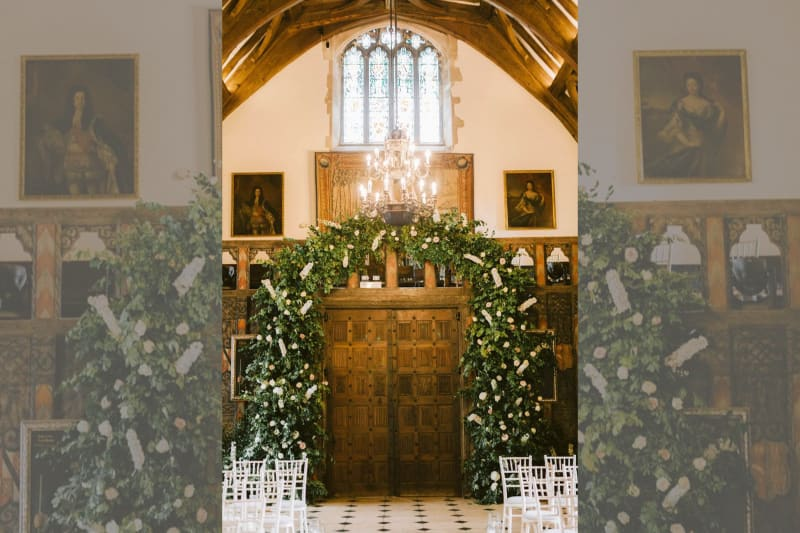 The ceremony room shows an archway covered in white flowers.