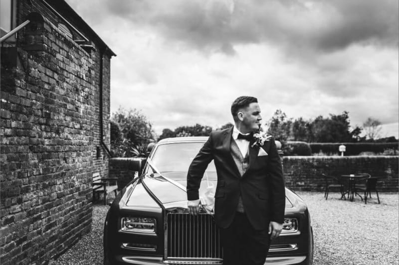 The groom leaning against a car.