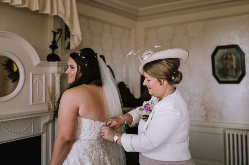 The mother of the bride zips her daughters dress.