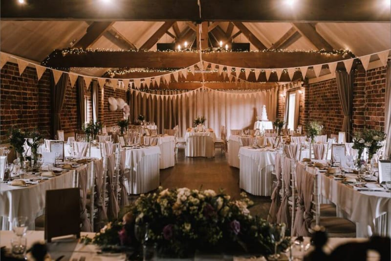 Inside the barn where the tables are set with a white cloth and flowers.