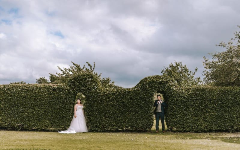 The bride and groom stand under a hedge outside.