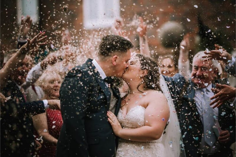 The bride and groom kiss as petals are thrown at them.