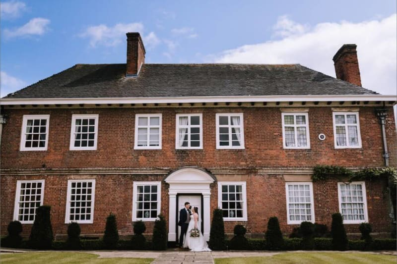 The bride and groom stand outside a big brick house with white windows.