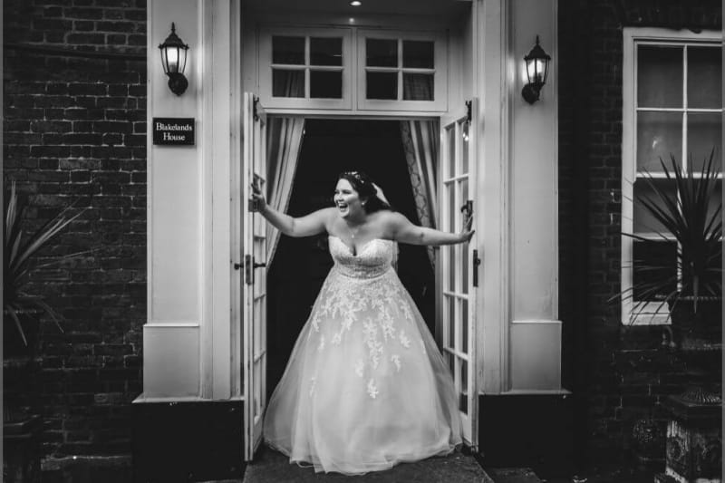 The bride laughing as she opens a white door.