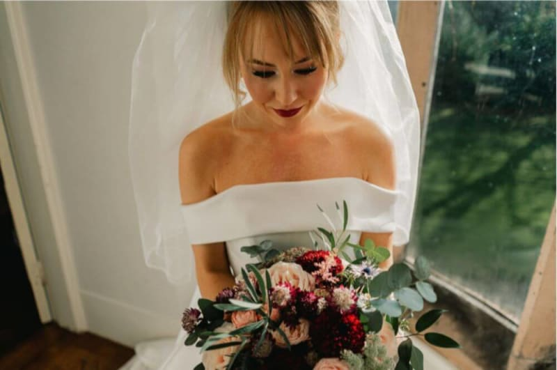 The bride is inside holding a bouquet.