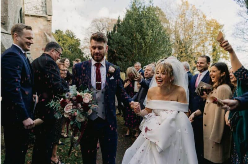 The guests throw petals to the couple as they laugh.