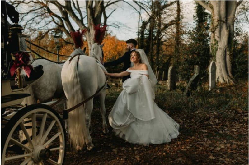 The bride and groom pet one of the horses that pulls the carriage.
