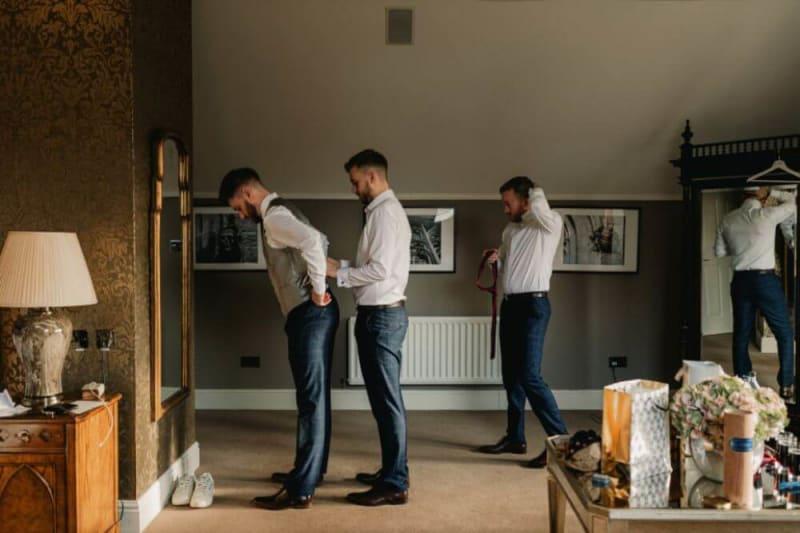 The groomsmen help the groom get dressed.