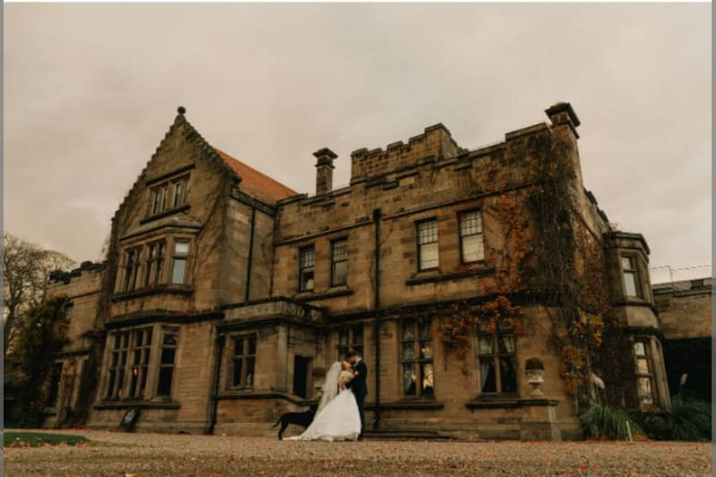 The bride and groom kiss in front of the building, which is made of stone. The colors are very autumnal.