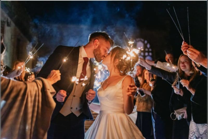 The bride and groom kiss outside at night as the guests hold candles.