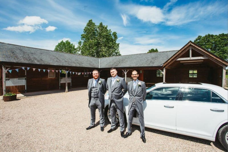 The groom and groomsmen stand next to a white car.