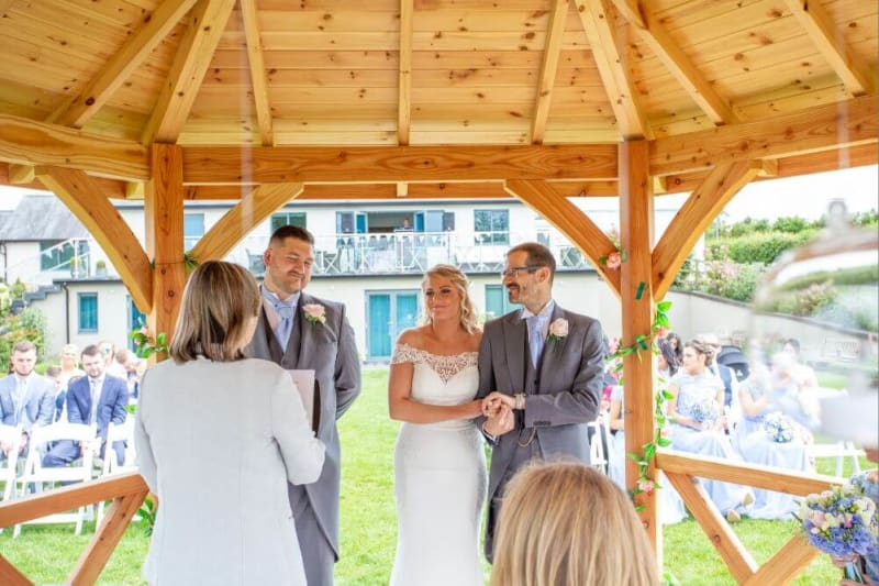 Inside the wooden gazebo in the garden, the bride is arm in arm with her father.