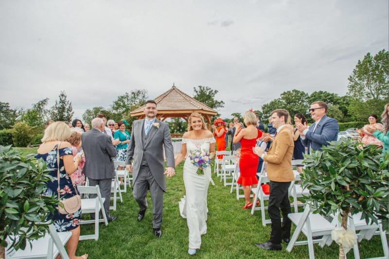 The couple walks down the aisle with people around them clapping.
