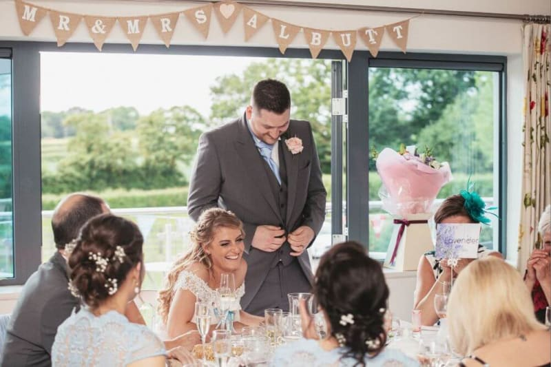 During the reception, the groom says something funny as the bride laughs.
