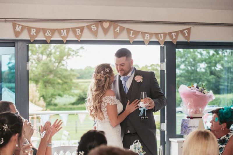The bride and groom stand facing each other with the groom holding a glass of champagne.