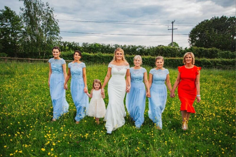 The bride holding hands with several women in blue and red and a little girl in white.