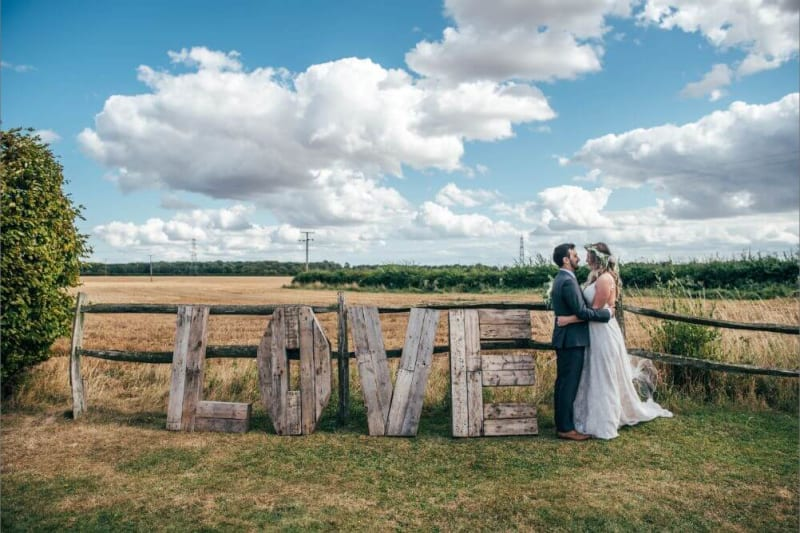 "The couple embrace next to a big wooden sign that spells ""LOVE""."