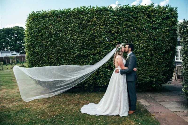 The bride and groom kiss in front of a big hedge.