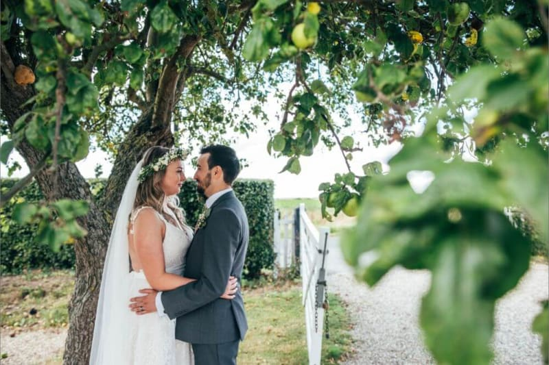 The couple stare lovingly at each other under a lemon tree.