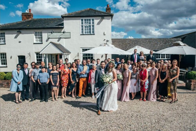 The couple and wedding guests stand in front of the house, that has a rustic yet contemporary style.