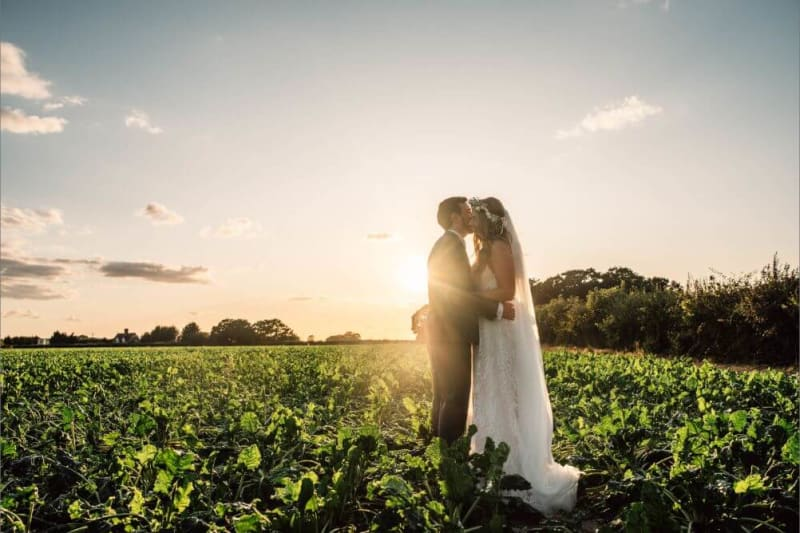 The groom gives the bride a peck on the cheek in the middle of a field.