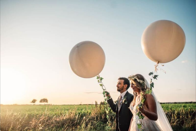 The bride and groom walk outside holding big white balloons.