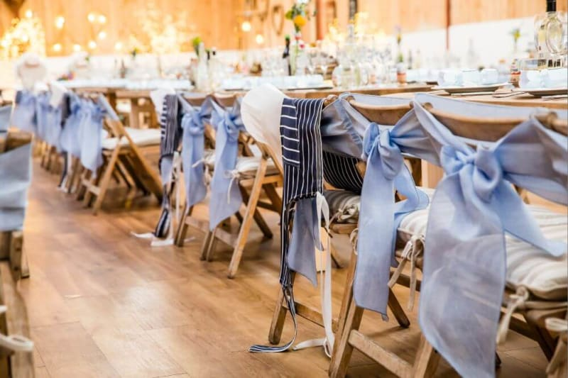 The dinner seats are decorated with blue ribbons.