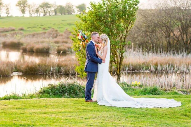 The couple kiss outside beside a lake.