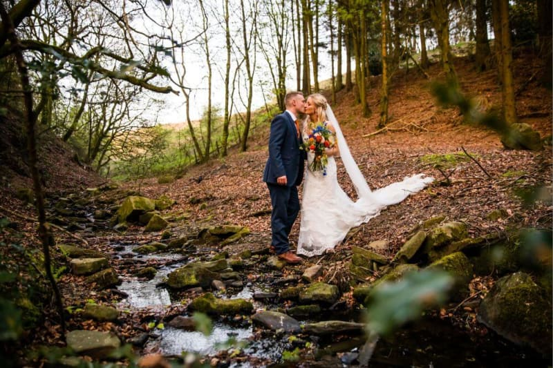 The couple kiss beside a stream in the woods.