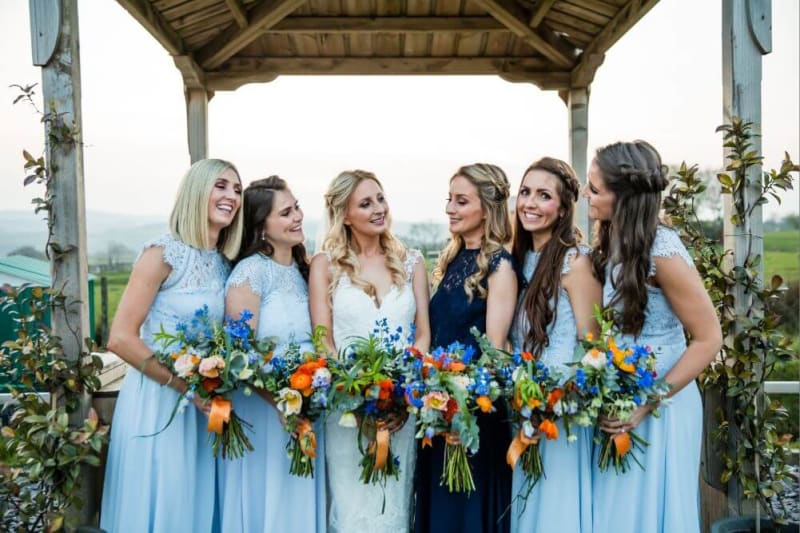The bride poses with her bridesmaids dressed in blue.
