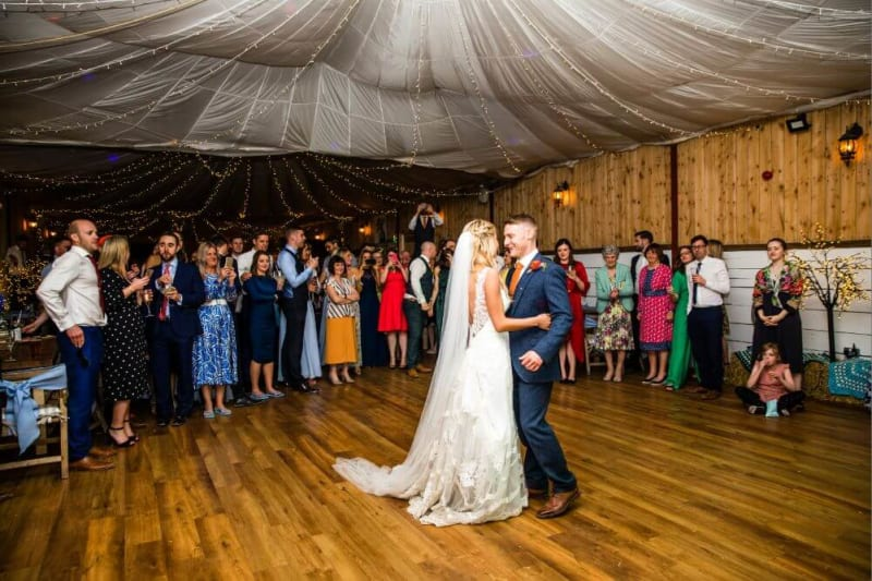 The couple dancing while guests look on.