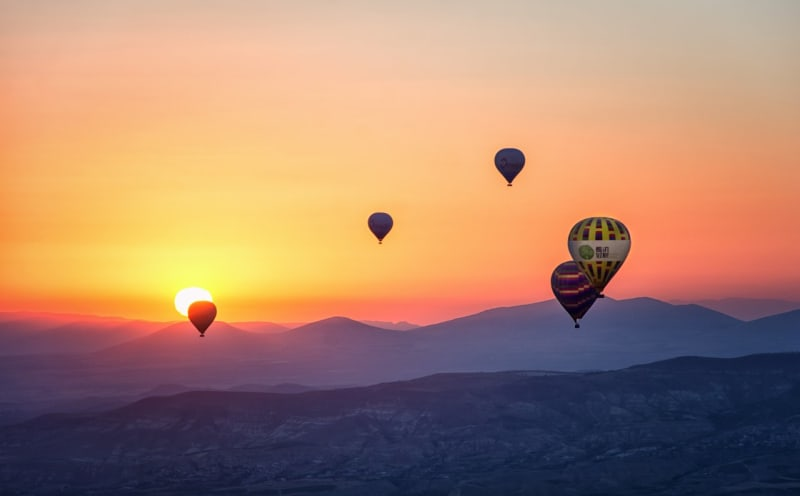 Hot air balloons in the air with a beautiful sunset in the background
